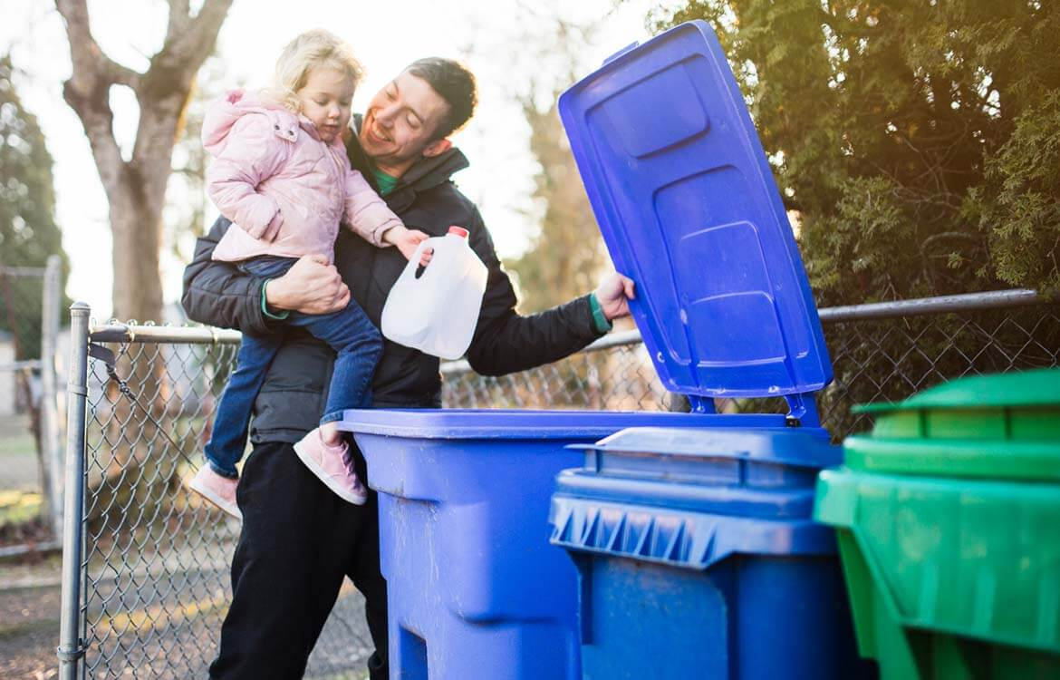 Why recycle - father and daughter put milk bottle into recycling bin