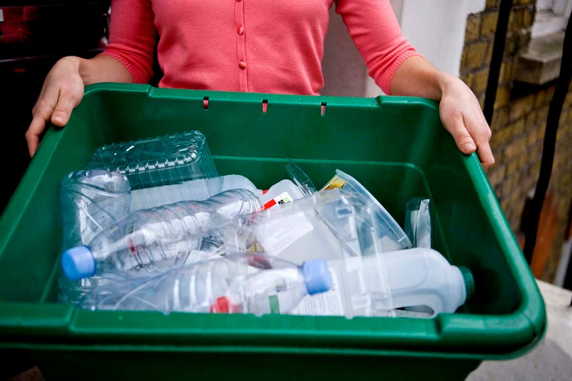Plastics recycling - woman holding recycling box