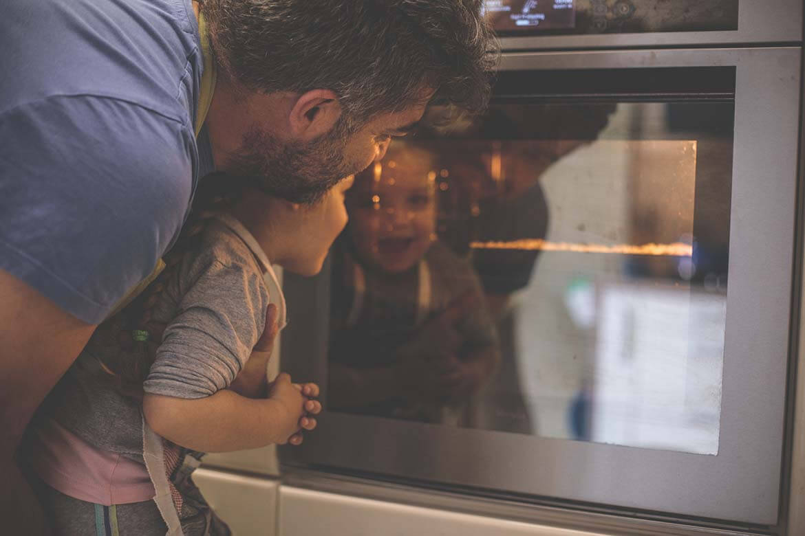 Father and son looking into oven to save energy in the kitchen
